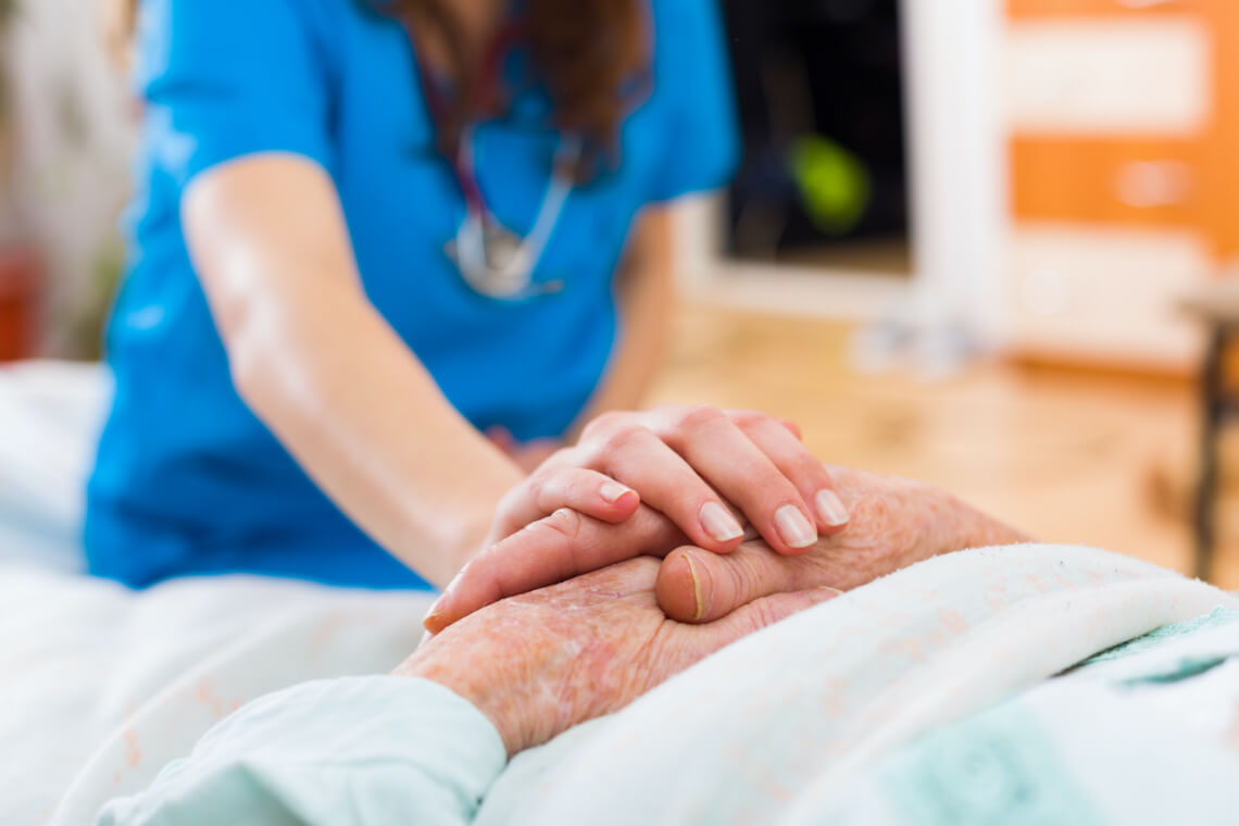 Elderly woman being cared for by a nurse in a long term health care facility.