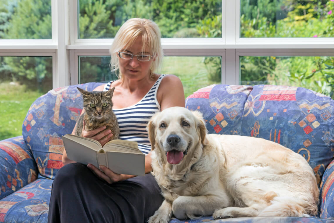 Woman relaxing in her home, with her house pets.